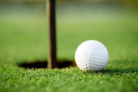 Golfbal en gat Stockfoto