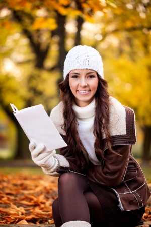 Smiling young woman with book in the autumn park photo