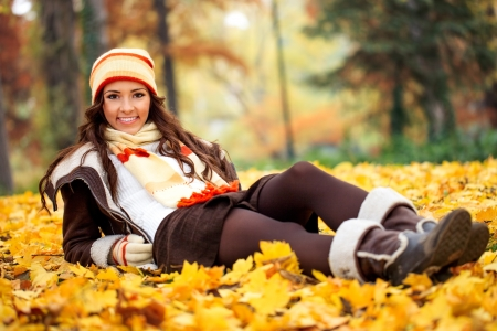smiling girl lying  autumn park on leaves photo
