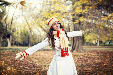 outstretched arms: young woman enjoying in autumn park, walking with outstretched arms