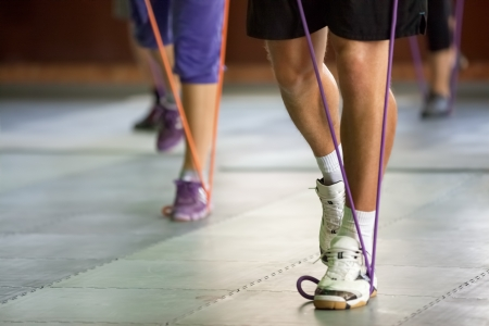 resistance: sports muscular legs with a resistance band,  exercising at gym