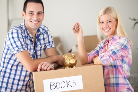 couple with piggy bank and keys with moving boxes, concept saving  photo