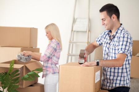 young couple packing moving boxes, ready for move out photo