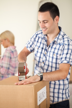 couple moving house, preparing moving boxes photo