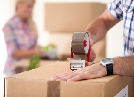 cardboard house:  Close up of male hand packing cardboard box, concept moving house Stock Photo