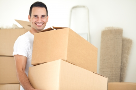 Smiling handsome man carrying packages during moving house photo