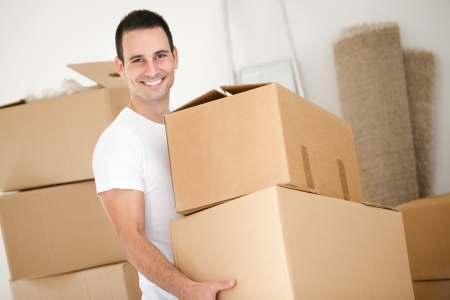 man carrying box: Cheerful young man holding  cardboard box Stock Photo