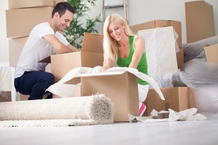 행복한 젊은 커플을 풀고 또는 상자 포장 및 새 집으로 이동.