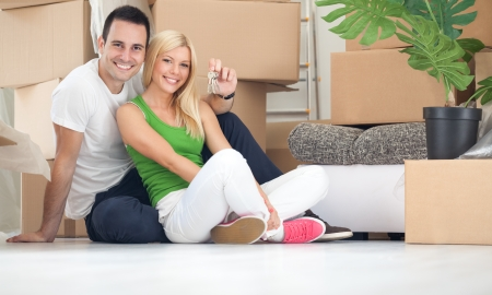 first move:  Portrait of happy couple with key of new home
