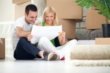 new house:  Man and woman looking at their house plans sitting in their new house Stock Photo