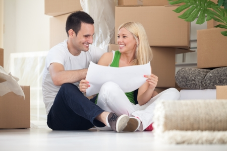 Attractive couple sitting on home floor looking at house plans and smiling at each other. photo