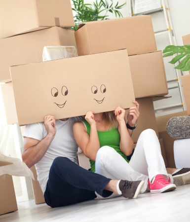 couple sitting on floor and having fun in their new house photo