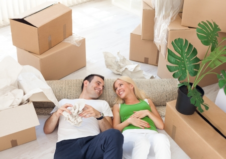 first home: Young smiling couple relaxing in the middle of cardboard boxes