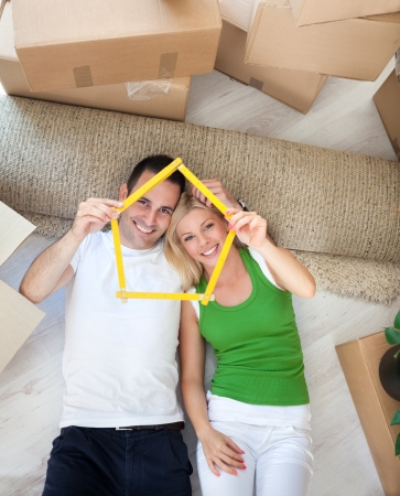 Couple lying on floor and looking  through a house-frame, enjoying in new house