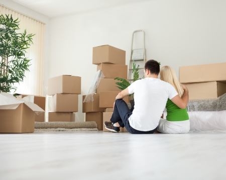 Young couple moving house resting in room full of boxes