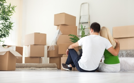 Couple sitting  and looking  lot of moving boxes, back view photo