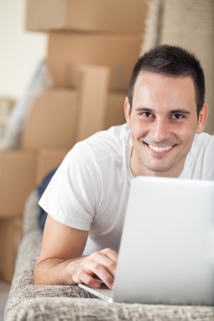 Young smiling man with laptop in new home photo