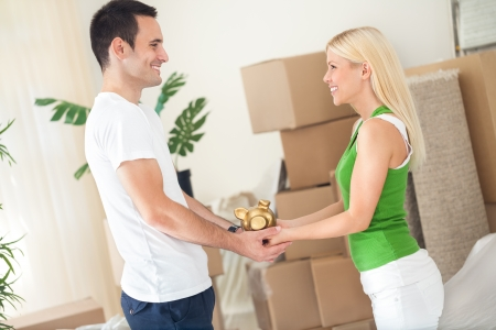 couple standing in new home  with piggybank  photo