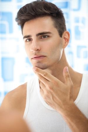 Man sieht an seinem Bart und dachte ?ber das Rasieren Standard-Bild