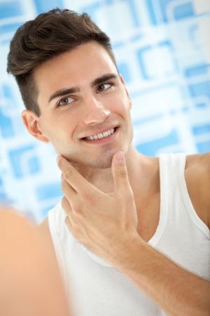 Jonge knappe ziet zichzelf in de badkamerspiegel