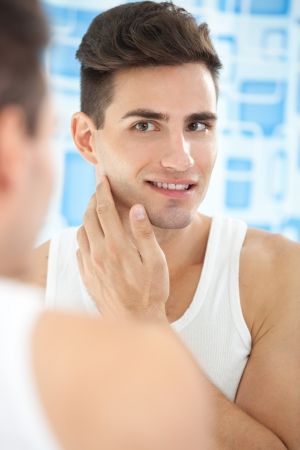 wash face:  Portrait of handsome man looking at mirror