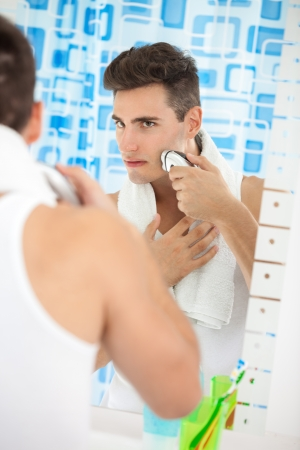 electric razor:  handsome young man shaving