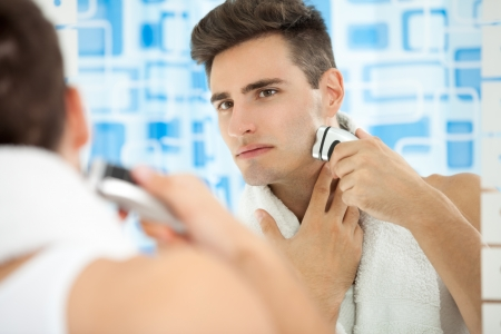 Young man shaving his beard off with an electric shaver photo