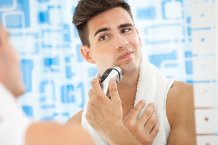 aftershave: Reflection of young man in mirror shaving with electric shaver Stock Photo