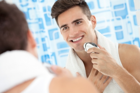 electric razor: Smiling young man using electric shaver front of mirror