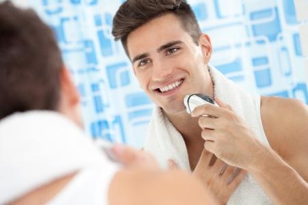 electric shaver: Sorridente giovane con rasoio elettrico davanti allo specchio