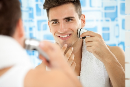 electric razor: Reflection of young man in mirror shaving with electric shaver Stock Photo