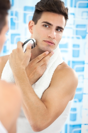 Close up of a young man shaving his beard off with an electric shaver photo