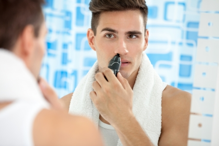handsome young man remove hair from his nose with trimmer photo