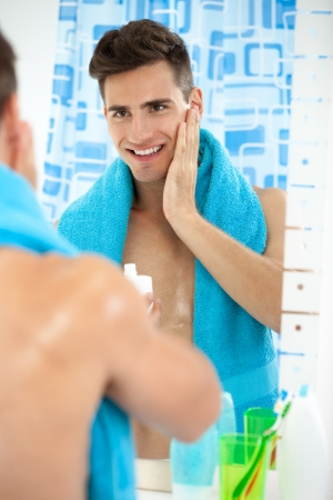 aftershave: Young handsome man applying aftershave, skincare Stock Photo