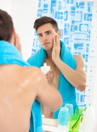 Portrait of a young handsome man applying after shave photo
