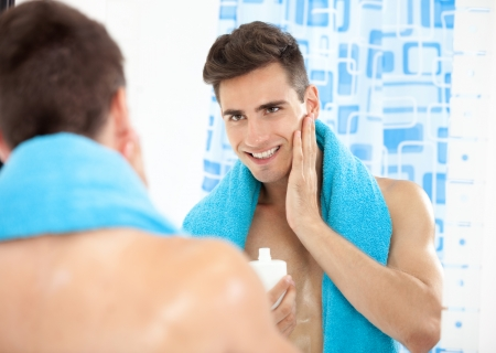 Portrait of a young man in the bathroom applying after shave photo