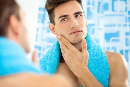 ひげそりの後彼の滑らかな顔に触れる若いハンサムな男