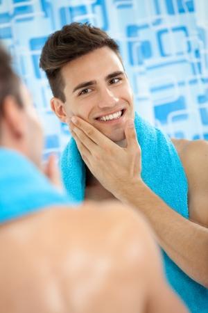 若い男性のひげそりの後彼のソフトの頬に触れる