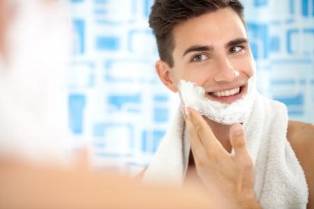 その日の準備をしている彼の顔を剃る男 写真素材