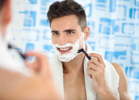 Happy laughing man shaving his face front of bathrooms mirror