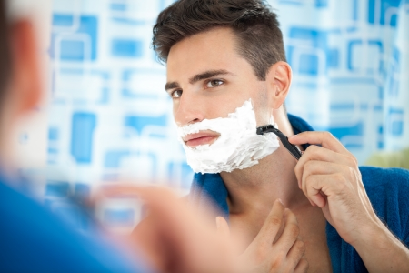 razor:  Close up of a young man shaving using a razor
