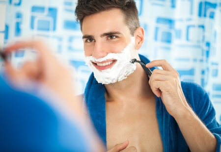 Sexy handsome young shaving and looking at himself in mirror