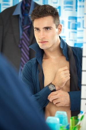 Sexy young businessman getting dressed in the morning with reflected at mirror photo