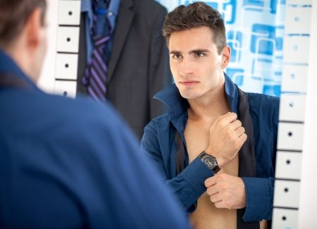 hurried: young man preparing for work, dressing up and looking himself in mirror Stock Photo