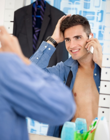Young man an looks himself at mirror while preparing for job  photo