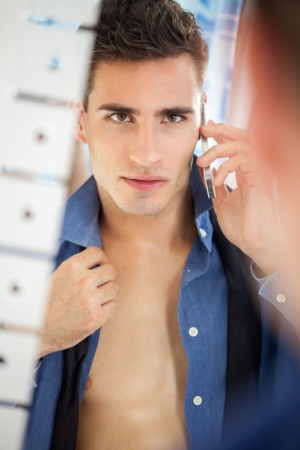 Sexy young men preparing for job looking at himself in mirror photo