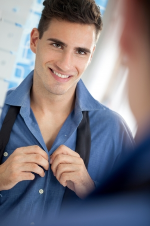get dressed: smiling young man to get dressed front of mirror in bathroom