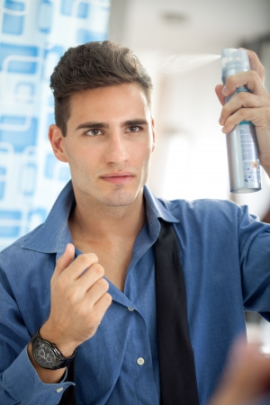 aftershave:  young man himself has makes hairstyle in bathroom Stock Photo