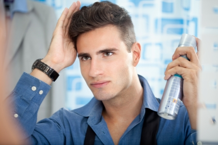 strong men: Young man applying hair spray to his hair.