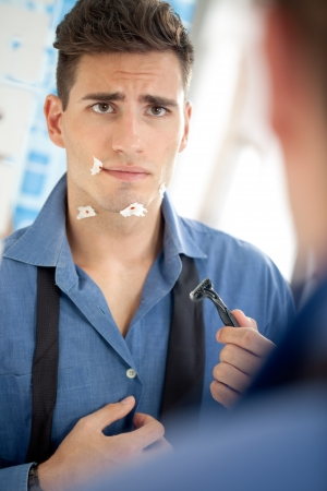 Unhappy young man looking his cuts on face after shaving
